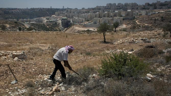 A Palestinian villager works on his land that overlooks the Israeli settlement of Mattityahu, background, in the West Bank village of Bilin near Ramallah, Wednesday, July 31, 2013. Pressing ahead in a new U.S.-backed push for Middle East peace, Israeli and Palestinian negotiators agreed Tuesday to meet again within two weeks to start substantive talks in hopes of reaching a long-elusive settlement within nine months. (AP Photo/Nasser Nasser)