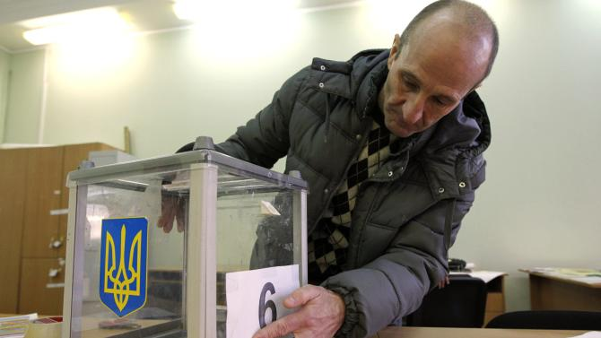 An election commission worker adjusts a number on a ballot box at a polling station in Kiev