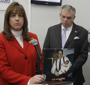Laura Dean Mooney, national president of Mothers Against Drunk Driving (MADD), holds up a photograph of her late husband Mike and their daughter as U.S. Transportation Secretary Ray LaHood stands behind her during a news conference announcing the new Driver Alcohol Detection System for Safety (DADSS) in Waltham, Mass., Friday morning, Jan. 28, 2011. Mooney's husband was killed 20 years ago by a drunk driver. (AP Photo/Stephan Savoia)