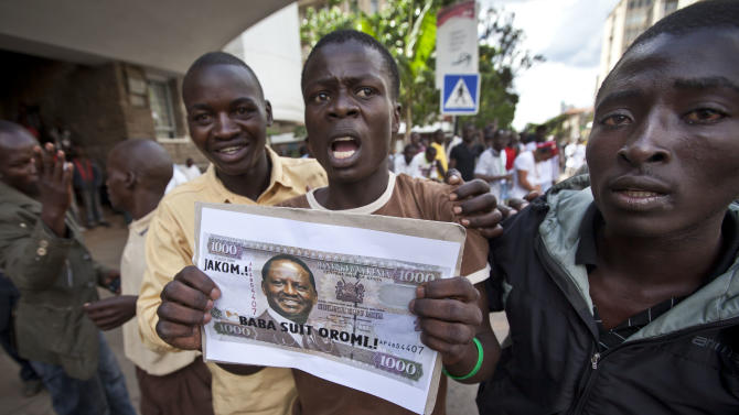 Supporters of losing presidential candidate Raila Odinga hold posters pretending to be banknotes with his face on, as they protest the verdict of the Supreme Court in Nairobi, Kenya Saturday, March 30, 2013. Kenya's Supreme Court on Saturday upheld the election of Uhuru Kenyatta as the country's next president, in a verdict on a petition by candidate Raila Odinga appealing the election result, ending an election season that riveted the nation amid fears of a repeat of the 2007-08 postelection violence. (AP Photo/Ben Curtis)