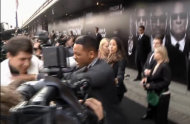 "In this video image taken from AP video U.S. actor Will Smith, center, pushes reporter Vitalii Sediuk, white suit, from the Ukrainian television channel 1+1 on the red carpet before the premiere of ""Men in Black III"" Friday May 18, 2012 in Moscow. Hollywood star Will Smith has slapped a male television reporter who tried to kiss him before the Moscow premiere of ""Men in Black III."" Smith pushed him away and then slapped him lightly across the cheek with the back of his left hand. (AP Photo via AP video)"