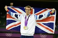 Britain's Andy Murray with his men's tennis singles gold medal on the podium at the London Olympics on August 5. Murray produced the performance of a lifetime to win his first Olympic gold medal with a crushing 6-2, 6-1, 6-4 demolition of world number one Roger Federer in the men's final on Sunday