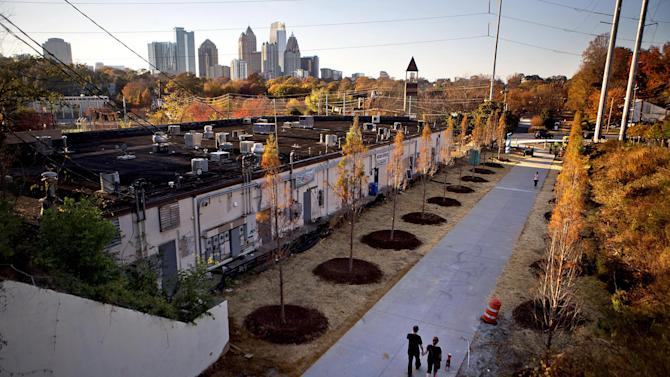 In this Nov. 20, 2012 photo, a couple walks along the Atlanta BeltLine as the midtown skyline stands in the background in Atlanta. Since an Atlanta nonprofit opened a 2.25-mile-long paved trail east of downtown last month, it has attracted a steady stream of joggers, dog-walkers and cyclists to take in spectacular views of the skyline as well as a slice of established neighborhoods that were once only seen by riding a freight train. The Eastside Trail is the latest and most visible phase of the Atlanta BeltLine, an ambitious $2.8 billion plan to transform a 22-mile railroad corridor that encircles Atlanta into a network of parks, trails, public art, affordable homes and ultimately streetcars. (AP Photo/David Goldman)