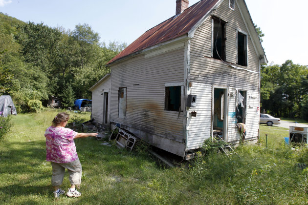 In this Aug. 17, 2012 photo, Janet Lumbra looks over the remains of her home in East Granville, Vt. For some, there will be block parties and parades. For others, a moment of silence. Or it might be just another day of struggling to clean up the mess. But if there's one unifying event to mark the first anniversary of Irene, it'll probably be the 30 seconds of ringing of bells in churches and town halls across Vermont that Gov. Peter Shumlin has requested for 7 p.m. Tuesday, Aug. 28, 2012, a year to the day after the storm changed Vermont forever.