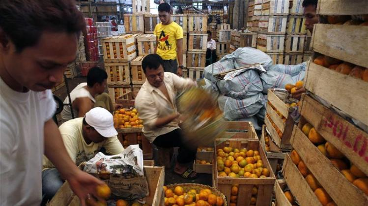 Workers sort out oranges at the Kramat Jati vegetable and fruit market in Jakarta