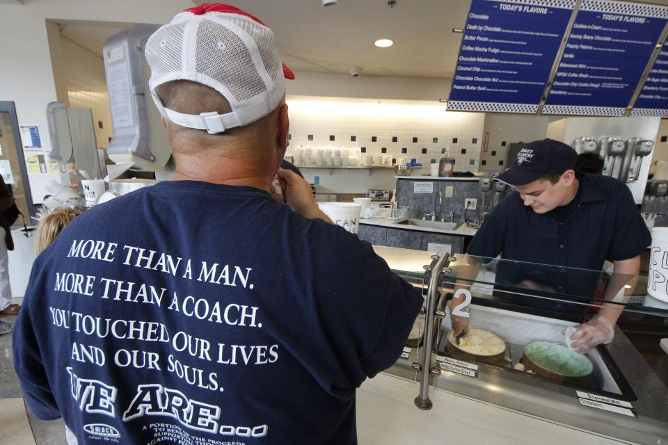 A cup of Peachy Paterno ice cream is scooped for a customer wearing a shirt memorializing former Penn State head football coach Joe Paterno at the Berkey Penn State Creamery on the main campus of Penn State University in State College, Pa., Friday, July 13, 2012. (AP Photo/Gene J. Puskar)