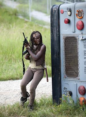 """FILE - This file publicity image released by AMC shows Danai Gurira as Michonne in a scene from the series """"The Walking Dead,"""" which resumes episodes from its fourth season on Feb. 9. When she's not killing zombies on the rural Georgia set of The Walking Dead, Gurira is in Atlanta shopping for costumes for her own production or directing performances of it in Zimbabwe. (AP Photo/AMC, Gene Page)"""