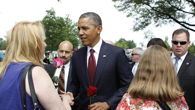 President Barack Obama greets visitors of Section 60 at Arlington National Cemetery on Memorial Day in Arlington, Va., Monday, May 27, 2013. Iraq and Afghanistan war veterans are buried in Section 60. (AP Photo/Molly Riley)