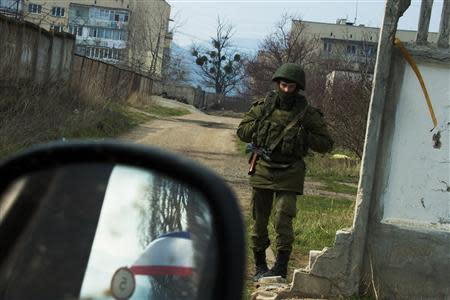 An armed man, believed to be Russian serviceman, stands guard outside Ukrainian military base in Perevalnoye