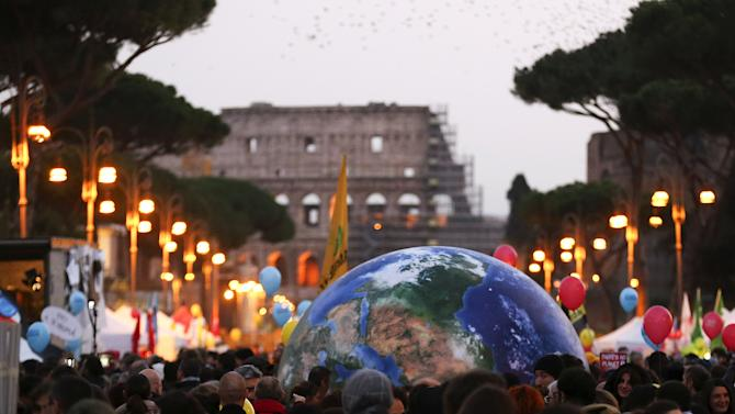 Protesters carry a globe-shaped balloon in front of Rome's Colosseum during a rally held the day before the start of the 2015 Paris Climate Change Conference (COP21), in Rome