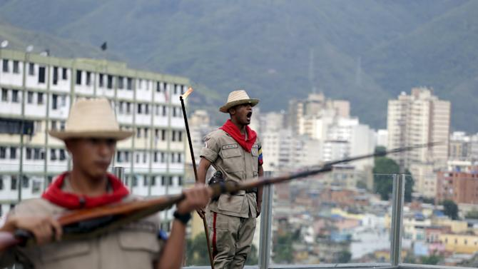 A soldier sings as he holds a stick with fire to shoot a cannon at 4:25 p.m., the time the death of Venezuela's late president Hugo Chavez was announced, at the 4F military fort in Caracas