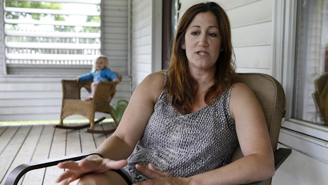 "In this June 2, 2014, photo, Shannon Spicker sits on her porch beside her daughter Maryana, 2, in Coraopolis, Pa., and talks about the feelings she had at the time of the O.J. Simpson arrest, trial and decision 20 years ago. Spicker said, ""Most of us didn't understand why it was racially charged."" (AP Photo/Keith Srakocic)"