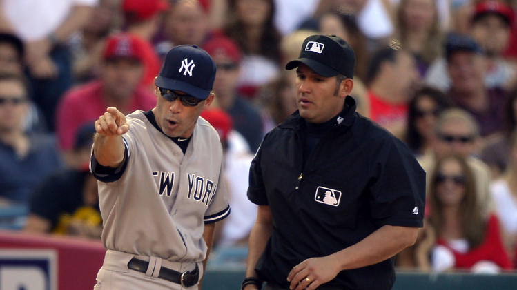 New York Yankees manager Joe Girardi, left, argues with third base umpire Manny Gonzalez after Yankees' Ichiro Suzuki was tagged out at third while trying to steal during the fourth inning of a baseball game against the Los Angeles Angels, Saturday, June 15, 2013, in Anaheim, Calif. (AP Photo/Mark J. Terrill)
