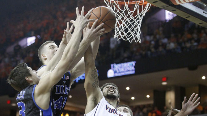 Virginia forward Anthony Gill (13) goes up for a layup alongside Duke guard Grayson Allen (3) and center Marshall Plumlee (40) during the first half of an NCAA basketball game in Charlottesville, Va., on Saturday, Jan. 31, 2015. (AP Photo/Ryan M. Kelly)