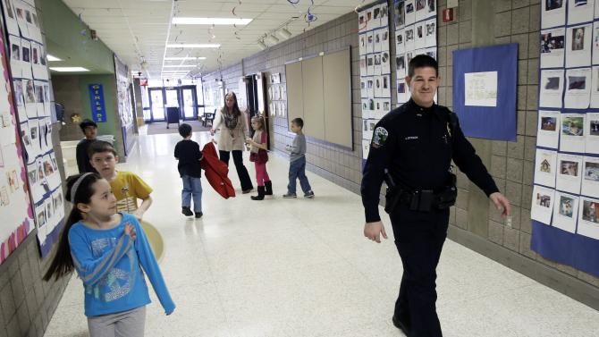 In a photo made Thursday, Feb. 21, 2013, a young girl, left, waves at police officer Jeff Strack as he walks the hallway of Jordan Elementary School in Jordan, Minn. In what is believed to be the first of its kind nationwide, the small city south of Minneapolis is taking school security to a new level by  setting up satellite offices inside the public school buildings. (AP Photo/Jim Mone)