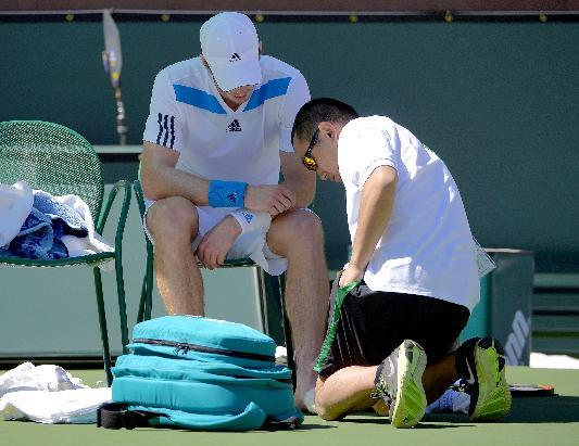 Andy Murray, left, of Great Britain, has his left foot checked on by a trainer during a match against Viri Vesely, of Czech Republic, during a third round match at the BNP Paribas Open tennis tourname