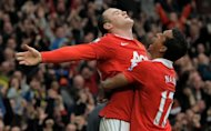 Manchester United's Wayne Rooney (L) celebrates with teammate Nani after scoring a goal during their English Premier League match against Manchester City at Old Trafford, on February 12, 2011