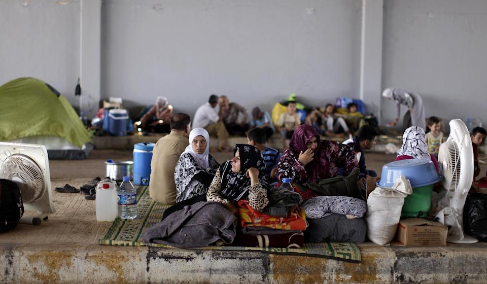Syrians, who fled their homes due to fighting between the Syrian army and the rebels, take refuge at the Bab Al-Salameh border crossing, in hopes of entering one of the refugee camps in Turkey, near the Syrian town of Azaz, Thursday, Aug. 30, 2012. (AP Photo/Muhammed Muheisen)