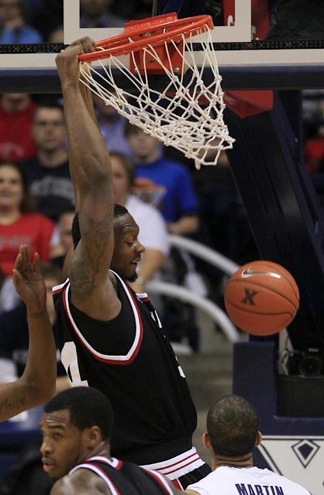 Cincinnati forward Yancy Gates, top, dunks against Xavier in the first half of an NCAA college basketball game, Saturday, Dec. 10, 2011, in Cincinnati. (AP Photo/Al Behrman)