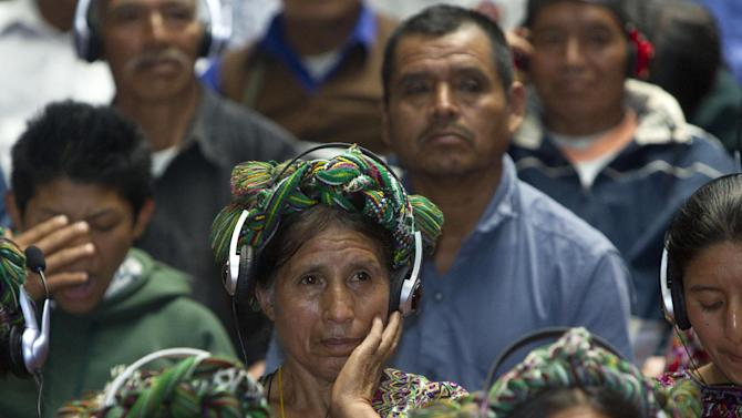 """An Ixil Indian woman, the relative of a civil war victim, uses earphones to hear translations between Spanish and the Ixil language during the genocide trial of former dictator Jose Efrain Rios Montt in Guatemala City, Thursday, May 9, 2013.  The 86-year-old ex-general says he never ordered attacks against """"a race,""""denying he ordered the extermination of Ixil Mayas. Prosecutors say that while in power, Rios Montt was aware of, and thus responsible for, the slaughter of at least 1,771 Ixil Mayas in the towns of San Juan Cotzal, San Gaspar Chajul and Santa Maria Nebaj in Guatemala's western highlands. (AP Photo/Moises Castillo)"""