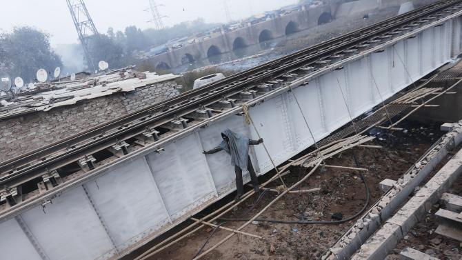 A worker stands at the repairing site of a railway track bridge on a winter morning in New Delhi