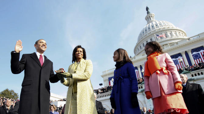 FILE - This Jan. 20, 2009 file photo shows Barack Obama, left, taking the oath of office from Chief Justice John Roberts, not seen, as his wife Michelle, holds the Lincoln Bible and daughters Sasha, right and Malia, look on at the U.S. Capitol in Washington. Michelle Obama is wearing a yellow sheath and coat by Isabel Toledo. Michelle Obama has proven her fashion savvy time and time again since she was introduced to the country as first lady on Inauguration Day 2009. In the past four years she has adeptly walked the line between directional fashionista and everywoman. (AP Photo/Chuck Kennedy, Pool, file)