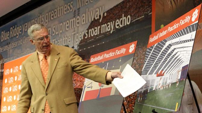 In this Jan. 14, 2011, file photo, Clemson athletic director Dr. Terry Don Phillips points at an architectural rendering of a proposed indoor football practice facility during a news conference in Clemson, S.C., where the university's athletic department announced their goal to invest $50 million over the next five years in capital projects. The master plan includes enhancements to facilities for football, baseball, basketball, soccer, tennis and golf.  Clemson opened the new indoor practice facilities in 2013