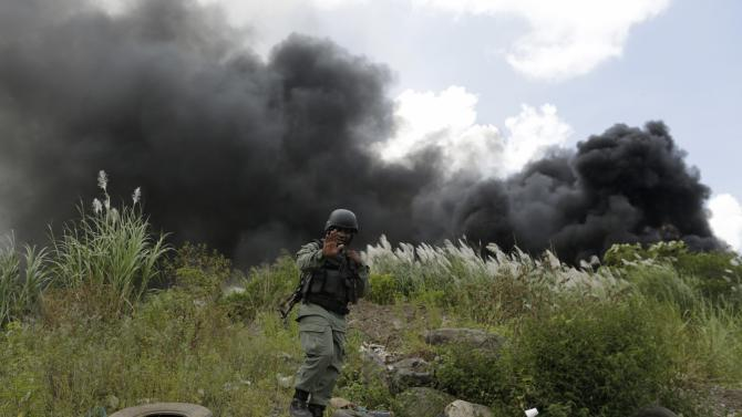 A police officer reacts as he guards the incineration of confiscated drugs in Panama City