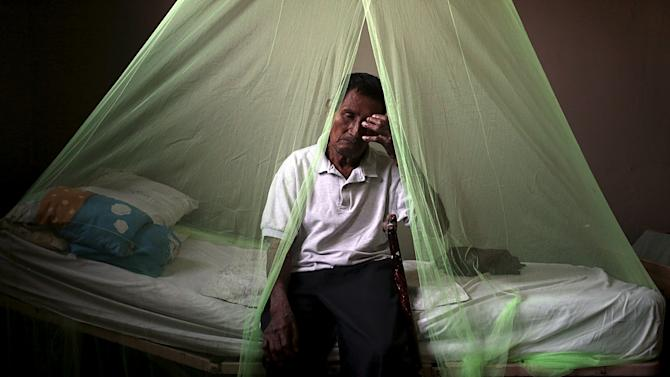 A man sits under a mosquito net in a home for the elderly in Masaya City