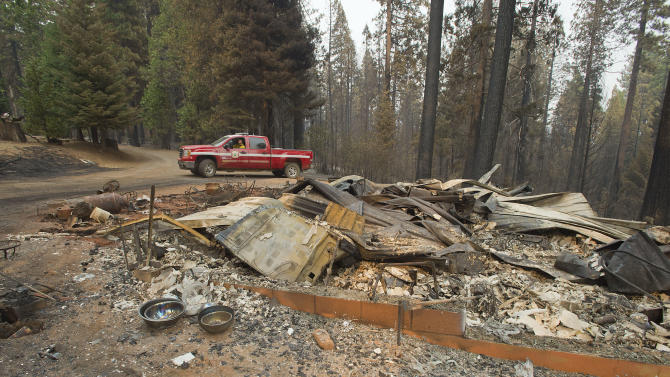 FILE - In a Friday, Sept. 19, 2014 file photo, a truck passes one of several homes that burned in the recent King fire near Icehouse in El Dorado County, Calif. Officials said Sunday, Sept. 21, 2014, that nearly three-dozen structures were destroyed in the massive Northern California wildfire that continues to spread more than a week after it started. (AP Photo/The Sacramento Bee, Randall Benton, File)