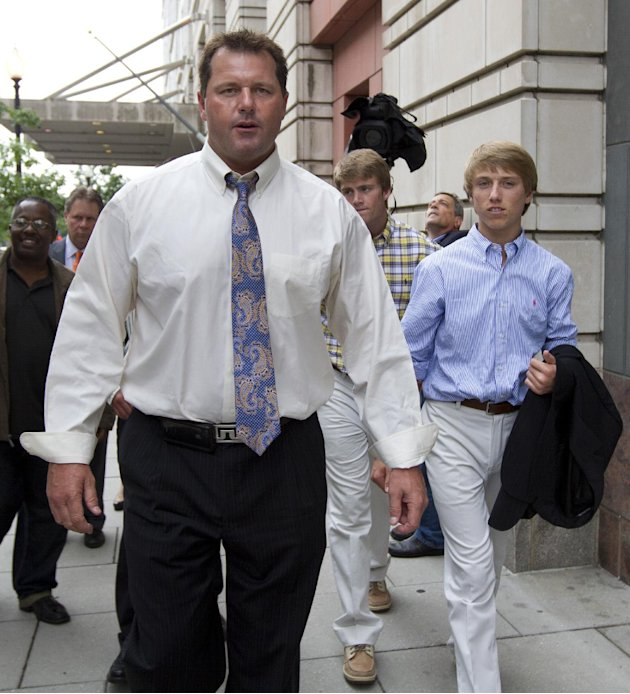 Former Major League Baseball pitcher Roger Clemens, left, gestures as he leaves Federal Court in Washington with sons, Kacy, center back, and Kody, right, Tuesday, June 12, 2012. Clemens' fate is in t