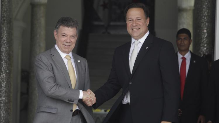 Colombian President Santos shakes hands with Panamanian President Varela at the presidential palace in Panama City