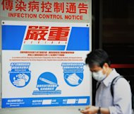A man walks past precautionary signs permanently posted at a hospital on April 27, 2009 in Hong Kong. China reported two human cases of bird flu in the southwestern city of Guiyang on Sunday, with both patients in a critical condition, the official Xinhua news agency said