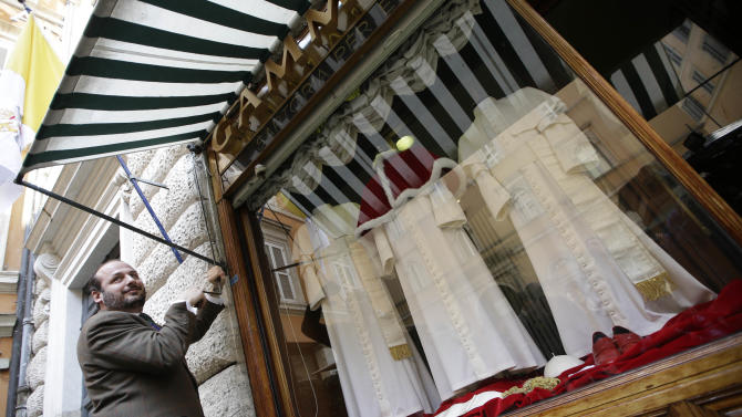 Shop owner Lorenzo Gammarelli, pulls out sun shades over his shop window where three sets of papal outfits - small, medium and large sizes - which will be sent to the Vatican for the new pope, are displayed, in Rome, Monday, March 4, 2013. For over a half century the Gammarelli family has produced the pope robes in three different sizes that are delivered before the conclave meets, in order to fit the newly elected popes. (AP Photo/Andrew Medichini)