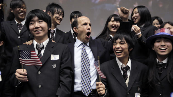 U.S. Ambassador to Japan John Roos, center, and Japanese high-school students celebrate reports that President Barack Obama won the presidential election at the U.S. Embassy in Tokyo Wednesday, Nov. 7, 2012. (AP Photo/Itsuo Inouye)