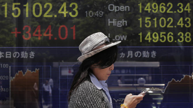 A woman walks by the electronic stock board of a securities firm in Tokyo, Wednesday, May 15, 2013. Enthusiasm on Wall Street sparked by another positive report on the U.S. economy helped push most Asian stock markets higher Wednesday. Japan's Nikkei 225 index surged 2.3 percent to 15,096.97. (AP Photo/Itsuo Inouye)