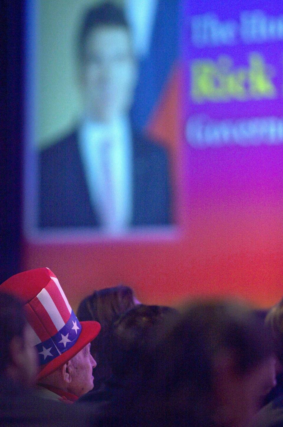 Longtime Mitt Romney supporter Oscar Poole of East Ellijay, Ga., looks on as Republican presidential candidate, Texas Gov. Rick Perry delivers a speech at the Georgia Legislative Briefing, Friday, Sept. 30, 2011, in Atlanta. (AP Photo/David Goldman)