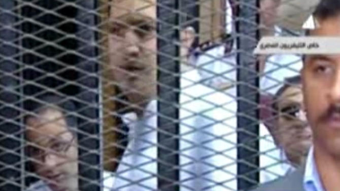 This image made from video broadcast on Egyptian state television shows former President Hosni Mubarak, right, and his sons Gamal, left,and Alaa, center inside the defendant's cage in a courtroom in Cairo, Egypt, Saturday, May 11, 2013. The retrial of former Egyptian President Hosni Mubarak resumed Saturday, with prosecutors requesting to present new evidence from a fact-finding commission's report that claims the ex-leader had full knowledge of the extent of the violence used against protesters. Mubarak is also facing corruption charges in the same case. He and his two sons, Alaa and Gamal, are accused of squandering public funds and abusing their power to sell land in a Red Sea resort area to business associate Hussein Salem at below market price in exchange for five villas there. (AP Photo/Egyptian State Television via AP video)