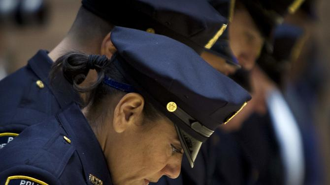 Police officers bow their heads during a New York Police Department Promotion Ceremony at Police Headquarters in the Manhattan borough of New York