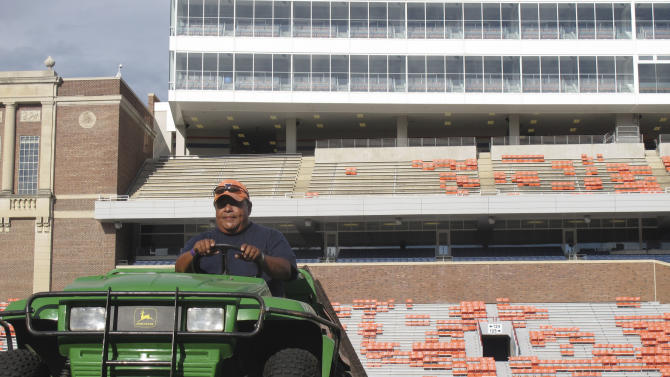 University of Illinois employee Ron Luna grooms the artificial turf at Memorial Stadium on Friday, Aug. 31, 2012 in Champaign, Ill. Illinois is scheduled to open the NCAA college football season on Saturday against Western Michigan. Forecasters say there could be a soaking that produces 6 to 8 inches or more of rain. But school officials say the brand-new turf can drain about 10 inches of rain an hour. (AP Photo/David Mercer)