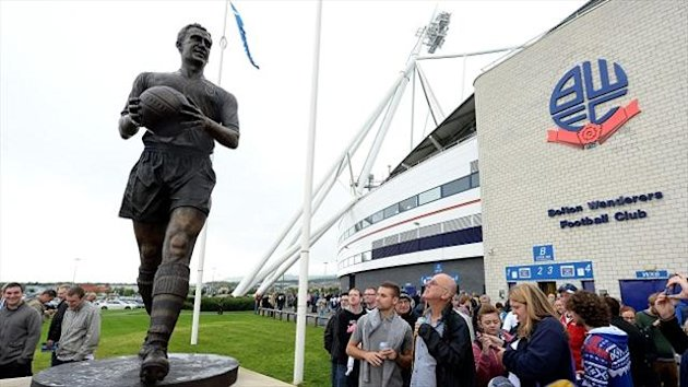 Fans look at the new Nat Lofthouse statue outside the the Reebok Stadium