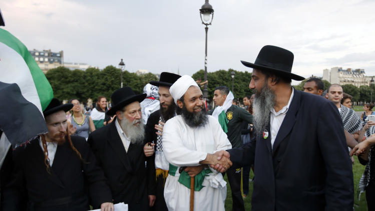 Orthodox Jews United Against Zionism pose with Muslim Sheikh Kamfan Faiz from Pakistan, center, in Paris, France, Wednesday, July 23, 2014 during a demonstration to protest against the Israeli army's shelling in the Gaza strip. Protesters marched through Paris against the Israel-Gaza war under the watch of hundreds of police in an authorized  demonstration days after two banned  protests degenerated into urban violence.(AP Photo/Francois Mori )