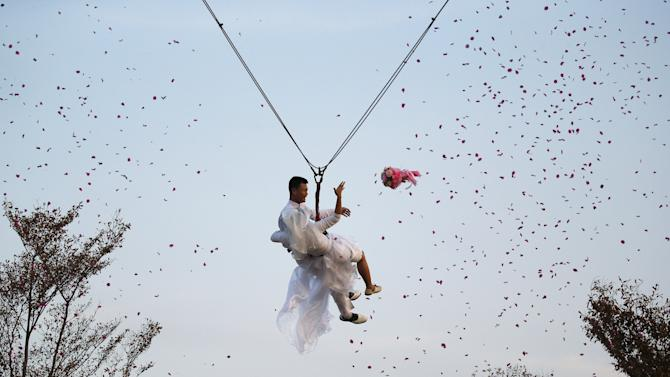 Groom Thipilindhra and his bride Laddawal throw a bouquet as they fly while attached to cables during a wedding ceremony ahead of Valentine's Day at a resort in Ratchaburi province