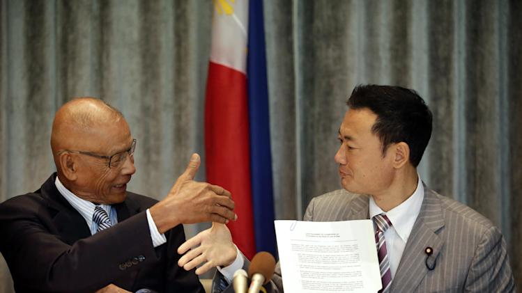 """Philippine Congressman Rodolfo Biazon, left, Chair of the House Committee on National Defense, and Hiroshi Nakada, Head of delegation of the Japanese opposition Party for Future Generations, shake hands shortly after signing a non-binding documents to reaffirm both countries to resolve the South China issues in peaceful ways and to respect international maritime laws, during a news conference Wednesday, Sept.3, 2014 at Makati, east of Manila, Philippines. In their press statement, Japan and the Philippines and some Southeast Asian nations, currently at odds with China over certain claims to some islands on the South and East China Sea, will work with other parliaments of other countries to """"maintain and promote international law and order of the sea."""" (AP Photo/Bullit Marquez)"""
