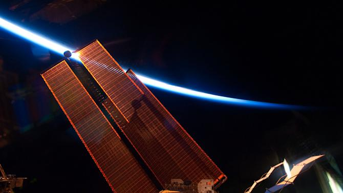 This image provided by NASA shows the intersecting thin line of Earth's atmosphere with the International Space Station's solar array wings photographed Thursday May 20, 2011 by an STS-134 crew member while space shuttle Endeavour remains docked with the station. (AP Photo/NASA)
