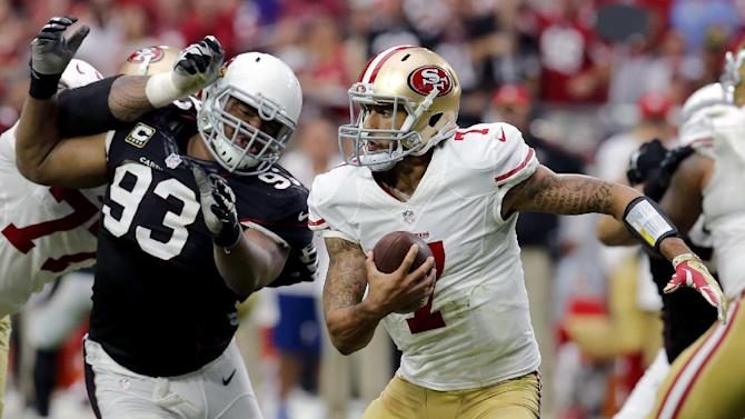 San Francisco 49ers quarterback Colin Kaepernick (7) tries to escape the pursuing Arizona Cardinals defensive end Calais Campbell (93) during the second half of an NFL football game, Sunday, Sept. 21, 2014, in Glendale, Ariz