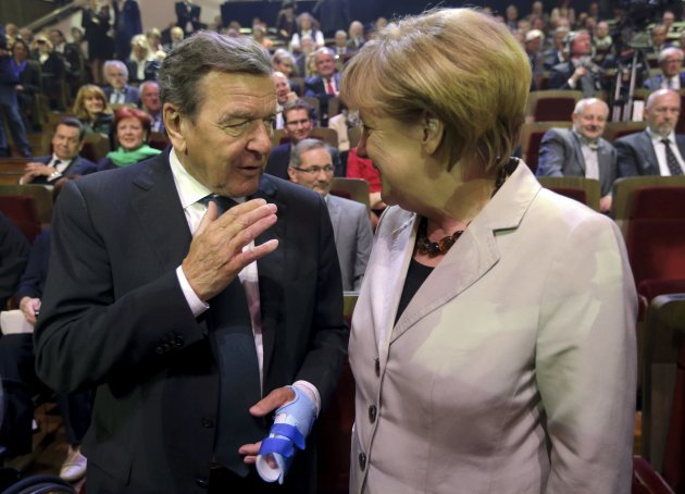German Chancellor Merkel speaks with former chancellor Schroeder at the Gewandhaus concert hall in Leipzig