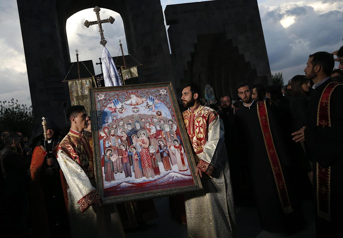 Priests carry an icon to attend a religious service in Echmiadzin, the religious center of the Armenian Church outside the capital Yerevan, Armenia, Thursday, April 23, 2015. On Friday, April 24, Armenians will mark the centenary of what historians estimate to be the slaughter of up to 1.5 million Armenians by Ottoman Turks, an event widely viewed by scholars as genocide. Turkey, however, denies the deaths constituted genocide and says the death toll has been inflated. The Armenian Apostolic Church, the country's dominant religion, held services Thursday to canonize all victims.  (AP Photo/Sergei Grits)