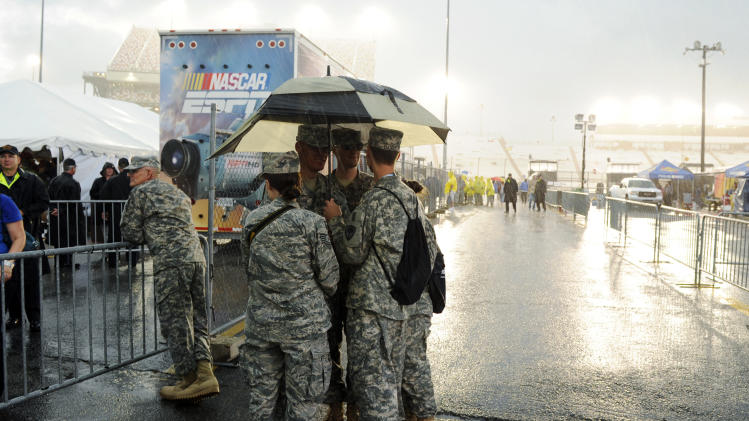 Members of the Virginia National Guard huddle under an umbrella as they wait for the start of the NASCAR Sprint Cup Series auto race at Richmond International Raceway in Richmond, Va., Saturday, Sept. 8, 2012. (AP Photo/Clem Britt)