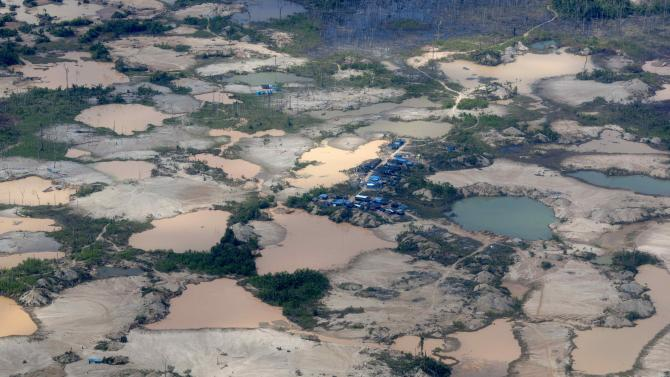 FILE - This Sept. 13, 2013 aerial file photo shows tailings produced by informal mining in Peru's Madre de Dios region. A study of mercury contamination from rampant informal gold mining in Peru's Amazon says indigenous people who get their protein mostly from fish are the most affected, particularly their children. The clock has run out for an estimated 40,000 illegal gold miners who had until Saturday to legalize their status in a region of southeastern Peru where fortune-seekers have ravaged rainforests and contaminated rivers. (AP Photo/Rodrigo Abd, File)